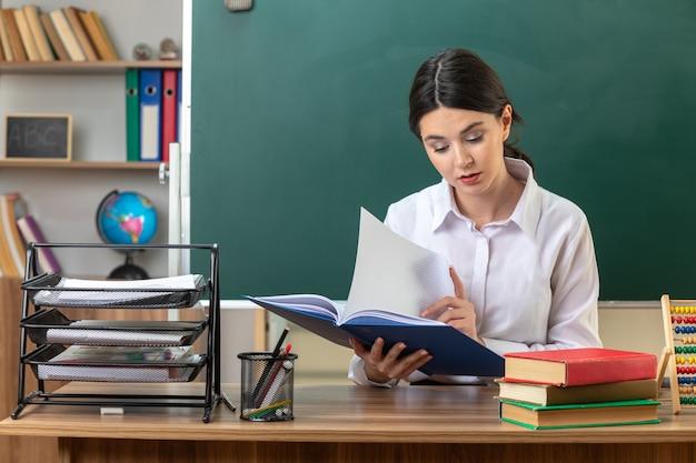 Cartella di lettura di una giovane insegnante femminile impressionata seduta al tavolo con gli strumenti della scuola in classe