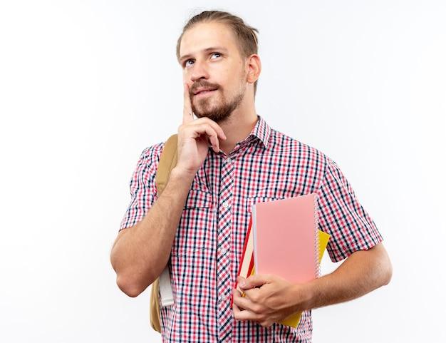 Impressionato giovane studente che indossa uno zaino con in mano libri che mettono il dito sul mento isolato sul muro bianco