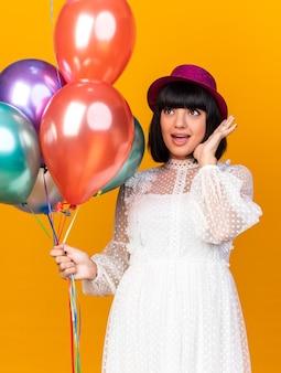 Una giovane ragazza impressionata che indossa un cappello da festa tiene in mano palloncini che guardano in alto mostrando la mano vuota vicino alla testa isolata sul muro arancione