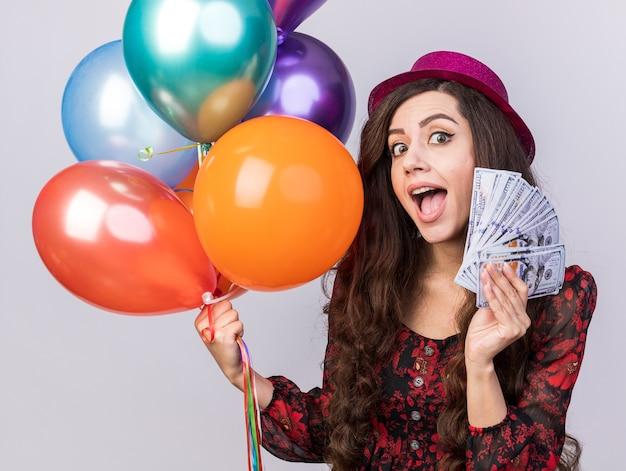 Ragazza giovane impressionata che indossa un cappello da festa che tiene palloncini e soldi guardando la telecamera isolata sul muro bianco