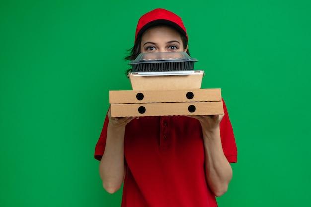 Impressionata giovane graziosa donna delle consegne che tiene in mano contenitori per alimenti e scatole per pizza