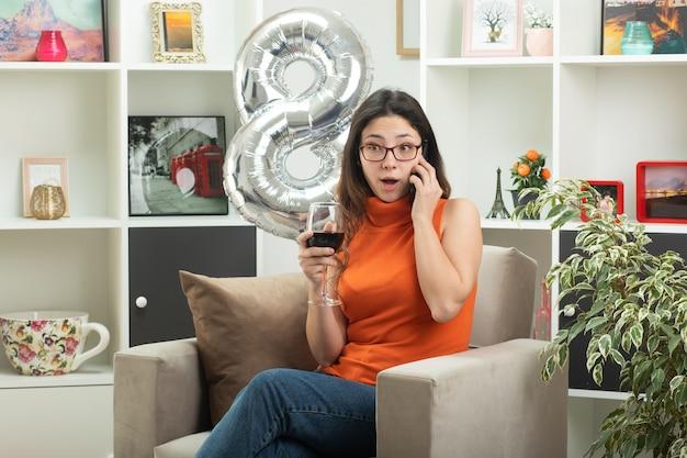Impressionato giovane bella donna con gli occhiali parlando al telefono e tenendo un bicchiere di vino seduto sulla poltrona in soggiorno a marzo giornata internazionale della donna
