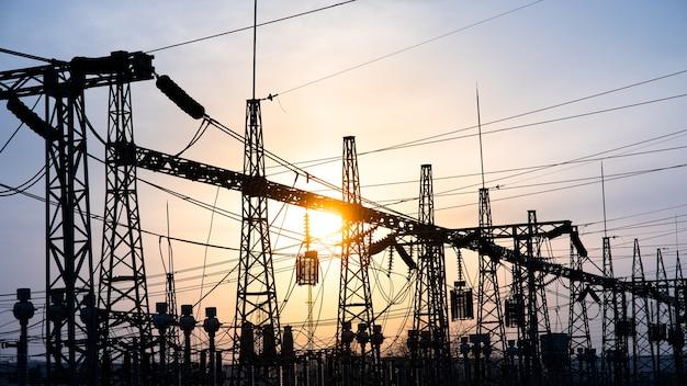 Rete di impressione alla stazione del trasformatore nel tramonto, alta tensione fino al cielo blu con tonalità blu, cornice orizzontale. stazioni di distribuzione elettrica