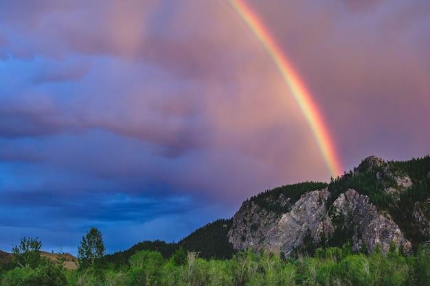 Un impressionante arcobaleno su una catena montuosa nella steppa kuray della repubblica di altai, russia