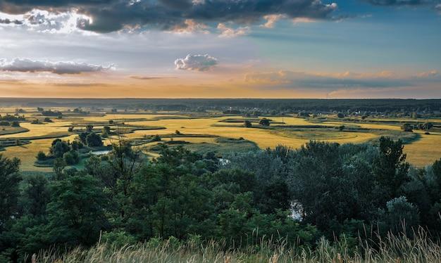 Impressionante cielo estivo colorato al tramonto, paesaggio di terreni agricoli vuoti, prati verdi, alberi e laghetto
