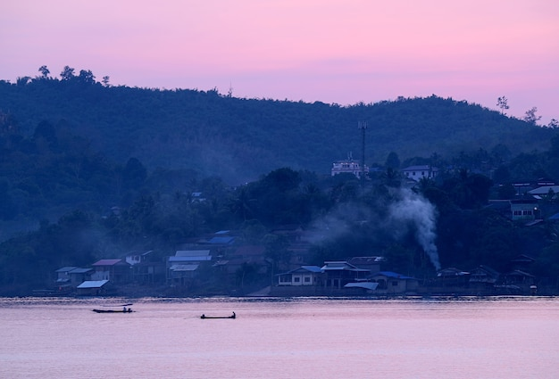 Impressionante vista al tramonto sul fiume di campagna con barche in corsa