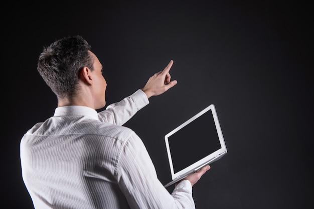 Tecnologia impressionante. uomo gentile positivo gioioso che tiene la sua mano e indica lo schermo digitale mentre è colpito dalla tecnologia moderna