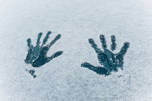 Impronta di due mani del palmo sulla trama della neve bianca. due impronte di mani umane su sfondo di vetro blu scuro congelato. concetto di divertimento invernale e attività di clima freddo. consistenza della neve. focalizzazione morbida