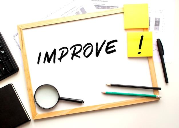 Migliorare il testo è scritto su una lavagna bianca. tavolo da lavoro con forniture per ufficio. business e concetto finanziario.