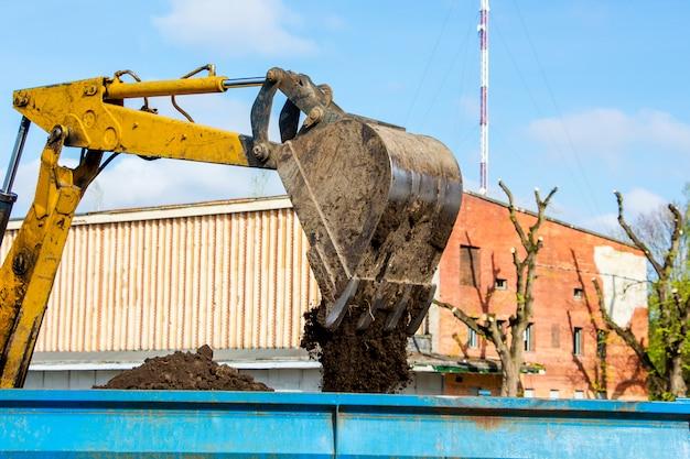 Miglioramento della città. la benna dell'escavatore versa la terra sul rimorchio del trattore