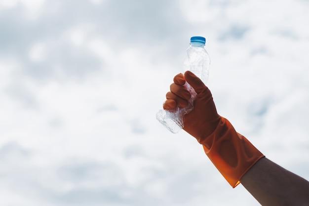 Miglioramento dell'ambiente gentili volontari ecocompatibili guanti arancioni che tengono in alto una bottiglia d'acqua di plastica