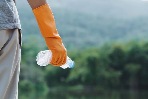 Migliorare l'ambiente gentili volontari ecologici guanti arancioni che tengono una bottiglia d'acqua di plastica
