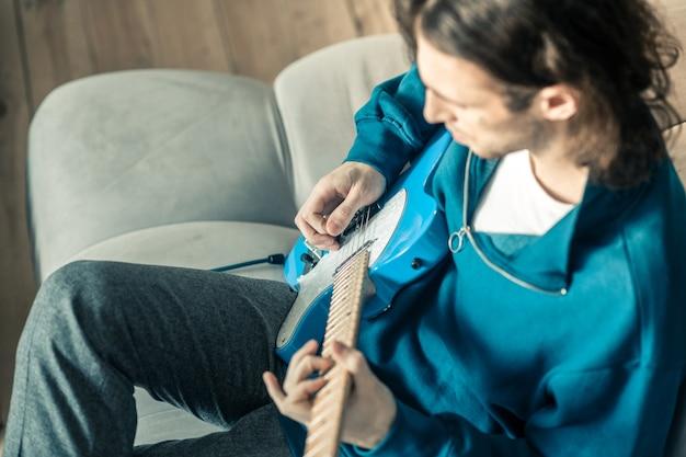 Migliorare le abilità. giovane musicista dai capelli lunghi con i capelli ondulati che suona con attenzione la chitarra mentre si riposa sul divano grigio