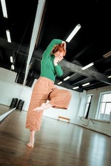 Improvvisazione. insegnante di danza professionale dai capelli rossi in piedi su una gamba sola mentre balla in studio