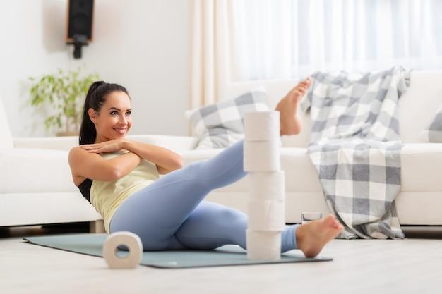 Improvvisare l'allenamento a casa degli addominali impilando la carta igienica e raggiungendo i piedi alla loro altezza.