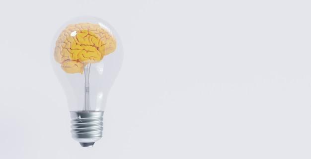 Lampadina a incandescenza con cervello giallo al suo interno su superficie bianca. concetto di idea
