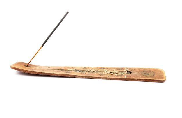Bastoncino di incenso dall'india su un supporto di legno su uno sfondo bianco Foto Premium