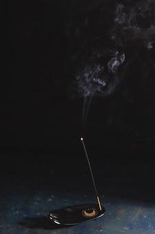 Un bastoncino di incenso su un poggiapolsi sta fumando su uno sfondo nero. copia spazio