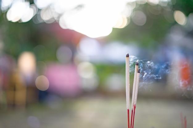 Bastoncini di incenso sulla pentola di joss stanno bruciando e il fumo è usato per pagare rispetto al buddha