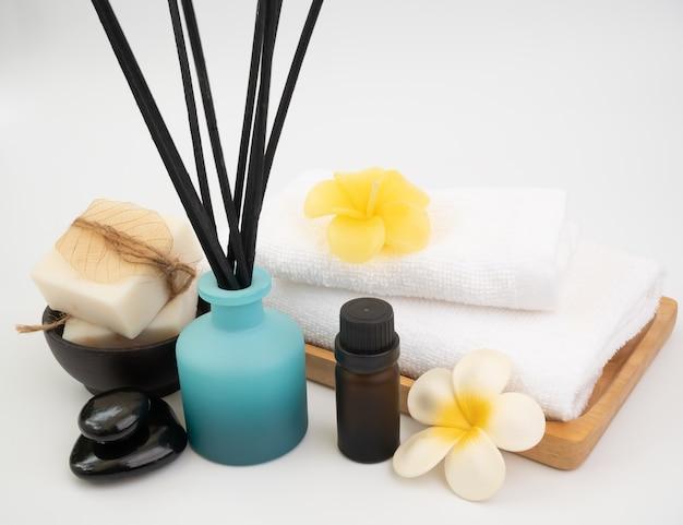 Bastoncini di incenso, fiore di plumaria, candela e asciugamani bianchi in spa o bagno su sfondo bianco, benessere termale con aromaterapia