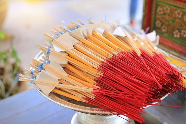 Bastoncini di incenso messo insieme una candela per pregare buddha.