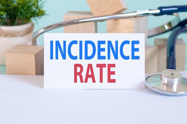 Parole di tasso di incidenza scritte su tessera sanitaria bianca, con stetoscopio, blocco di legno fiore verde.