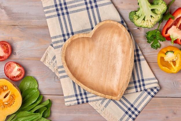 Includi verdure biologiche fresche e disco cuore in legno su pavimento in legno con spazio per copia ancora in vita