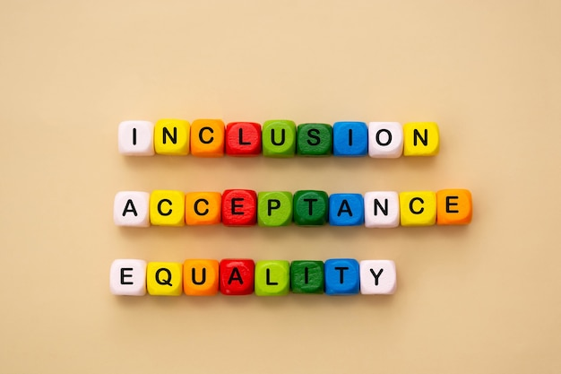 Parole di inclusione, accettazione e uguaglianza realizzate con cubi di legno colorati. concetto sociale inclusivo e di tolleranza, piatto.