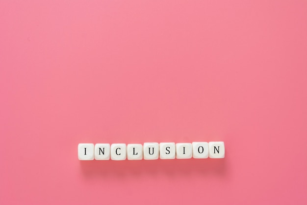 Testo di inclusione fatto da cubi di legno sul tavolo rosa. concetto sociale inclusivo. copia spazio.