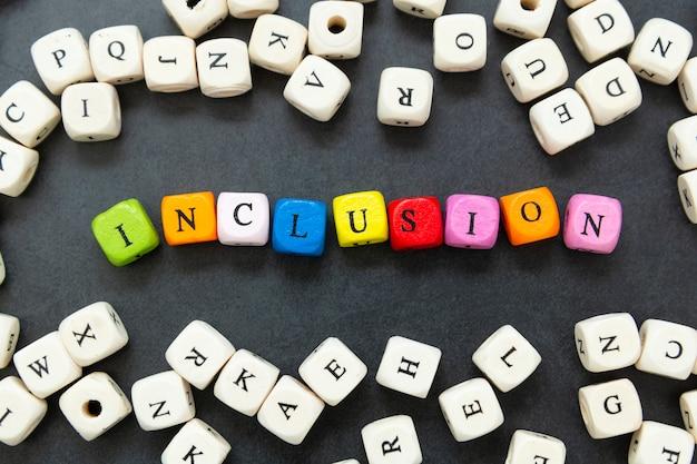Testo di inclusione di multi cubi colorati su sfondo scuro. concetto sociale inclusivo.