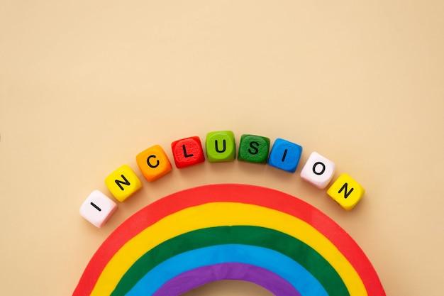 Parola di inclusione, cubi di legno colorati. concetto sociale inclusivo, tolleranza e accettazione, piatto.