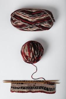 Progetto di lavoro a maglia incompleto con gomitolo di lana isolato