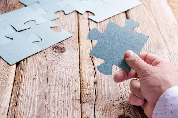 Puzzle incompleti che si trovano su tavole rustiche di legno. concettuale di innovazione, ricerca di soluzioni e integrazione. mano con pezzo di puzzle