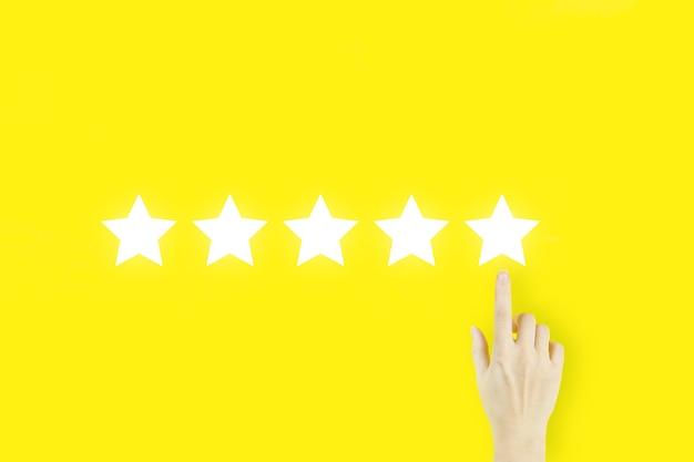Aumentare la valutazione del rating e il concetto di classificazione. concetto di esperienza del cliente. il dito della mano della giovane donna che indica con l'ologramma cinque stelle su fondo giallo.
