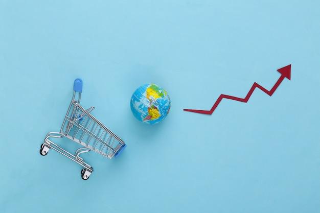 Aumento degli acquisti globali. carrello del supermercato con un globo, freccia di crescita che tende verso l'alto sul blu.