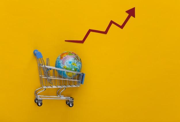 Aumento degli acquisti globali. carrello del supermercato con un globo, freccia di crescita che tende verso l'alto su un giallo.