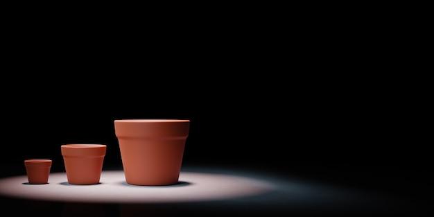 Vaso di fiori vuoto di dimensione crescente messo in evidenza su sfondo nero