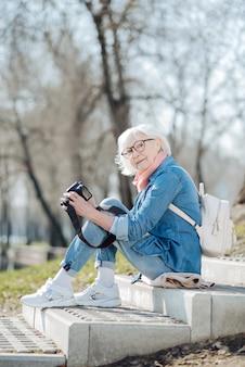 Giornata incredibile. gioiosa donna matura seduta sui gradini e guardando attraverso le foto