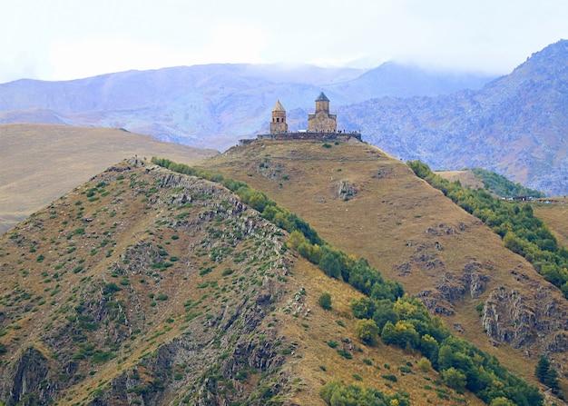 Incredibile vista della chiesa della trinità di gergeti sulla collina stepantsminda town georgia