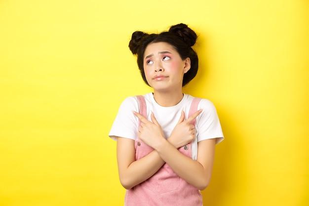 Ragazza adolescente asiatica indecisa preoccupata per fare una scelta, indicando di lato e guardando il logo confuso, in piedi sul giallo.