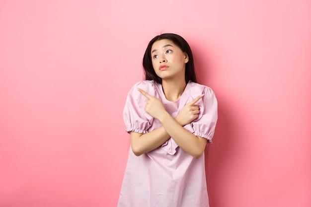 La donna asiatica indecisa non può decidere di puntare il dito di lato e guardare pensierosa da parte facendo la scelta...