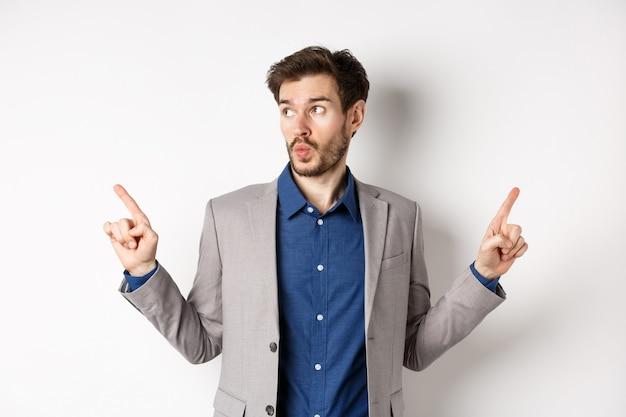 Imprenditore maschio indeciso in tuta che punta le dita lateralmente, scegliendo tra due varianti, guardando pensieroso il logo sinistro, in piedi su sfondo bianco.