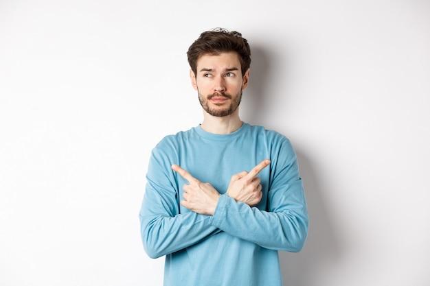 Uomo indeciso che fa la scelta, punta il dito lateralmente verso due varianti e decide, guardando pensieroso a sinistra, in piedi su sfondo bianco.