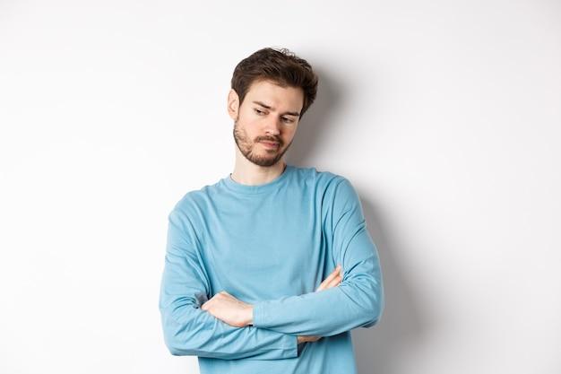 Uomo barbuto indeciso e premuroso che pensa, guarda pensieroso e fa la scelta, in piedi su sfondo bianco