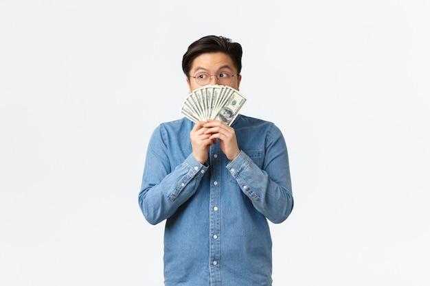 Indeciso giovane asiatico con gli occhiali che guarda dietro i soldi guarda lontano pensieroso pensando a come investire ...