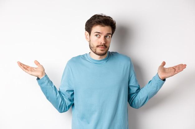 Giovane indeciso con la barba, alzando le spalle e non sa niente, guardando lontano confuso, in piedi in camicia blu su sfondo bianco