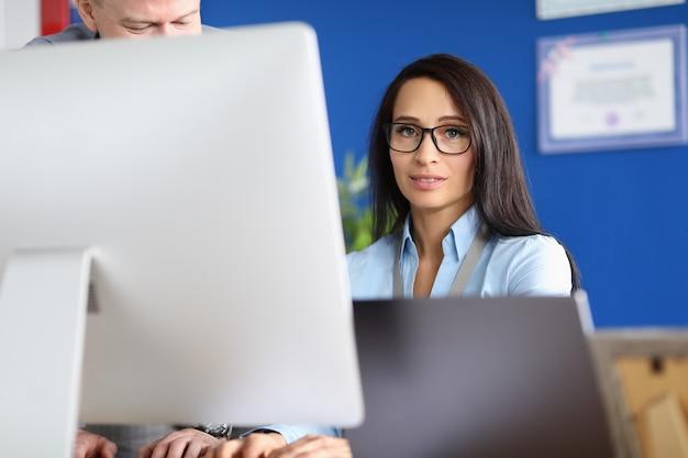La giovane donna non decisiva in vetri si siede al computer