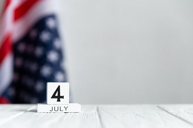 Giorno dell'indipendenza, il quattro luglio, calendario sullo sfondo della bandiera degli stati uniti e tavolo in legno bianco