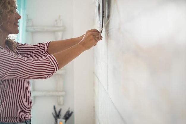 Donna indipendente che lavora a casa riparando cose sul muro bianco nella stanza - concetto di lavoro fai da te all'interno della casa -