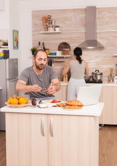 Lavoratore dell'indipendenza che fa colazione e lavora da casa mentre sua moglie cucina. libero professionista che lavora a distanza, parla in videoconferenza videochiamata online web meeting internet da casa, comunicazione d